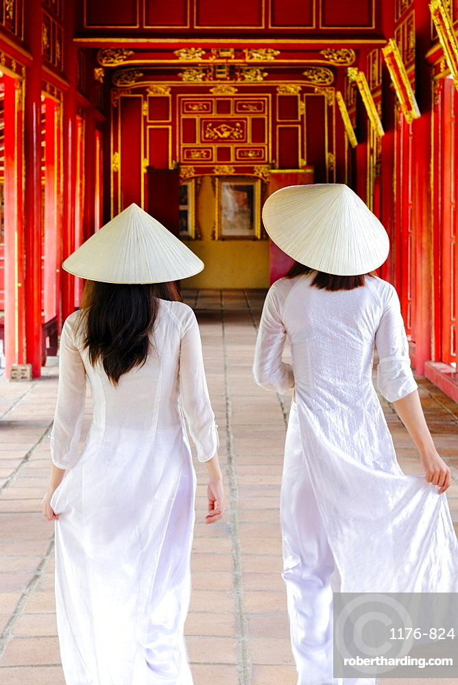 Two Vietnamese women in traditional Ao Dai dresses and Non La conical hats in the Forbidden Purple City of Hue, Thua Thien Hue, Vietnam, Indochina, Southeast Asia, Asia