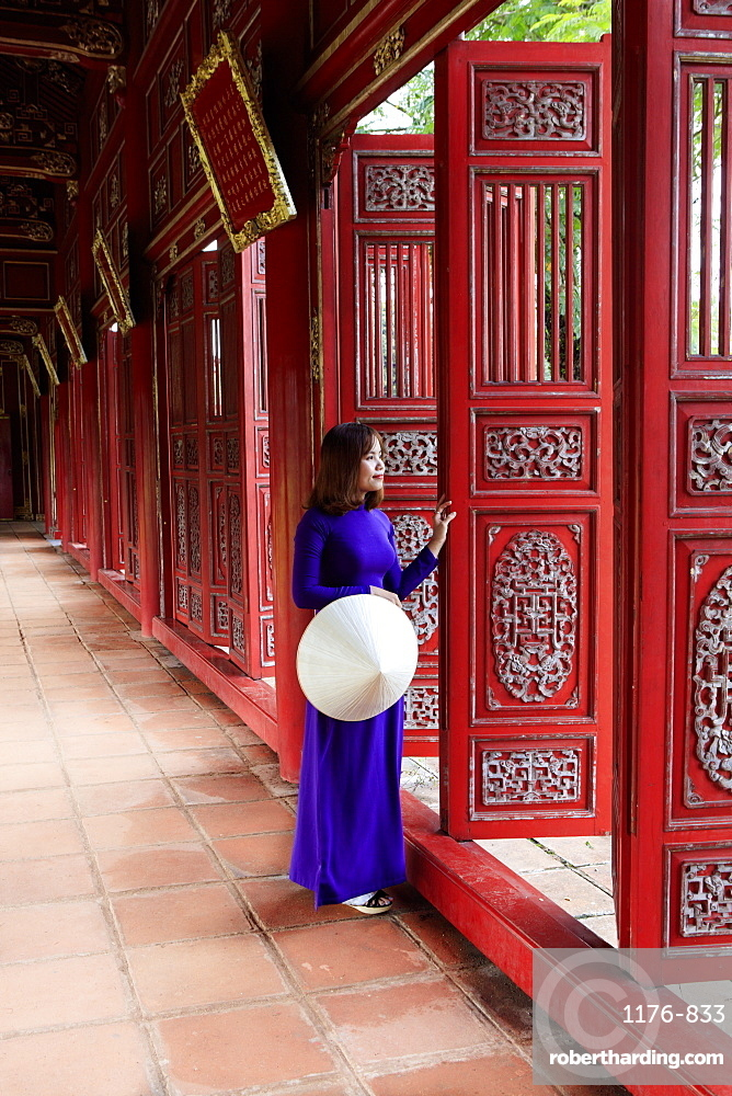 A woman in a traditional Ao Dai dress and Non La conical hat in the Forbidden Purple City of Hue, A Unesco World Heritage Site