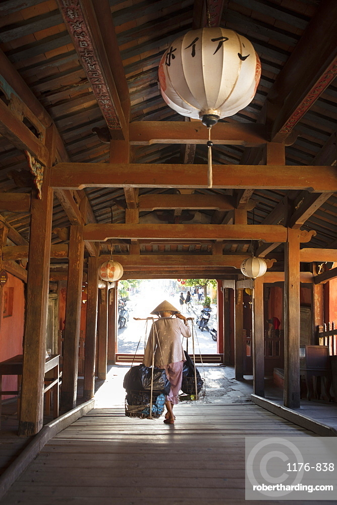 A woman carrying bags on a hod through the covered Japanese bridge in Hoi An, Quang Nam, Vietnam, Indochina, Southeast Asia, Asia
