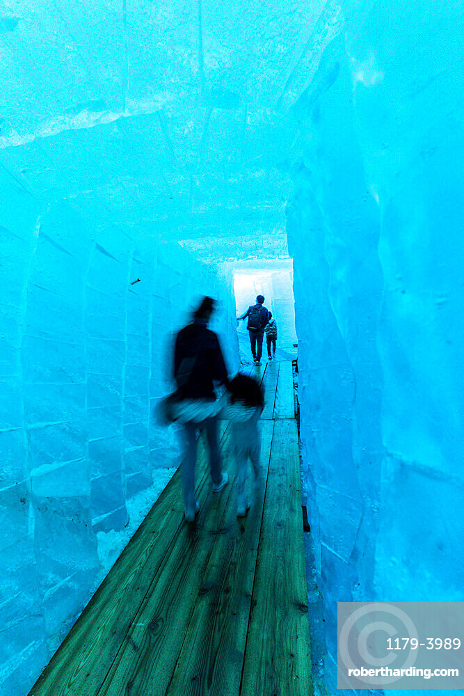 Tourists walking in the ice grotto inside Rhone Glacier, Gletsch, Canton of Valais, Switzerland