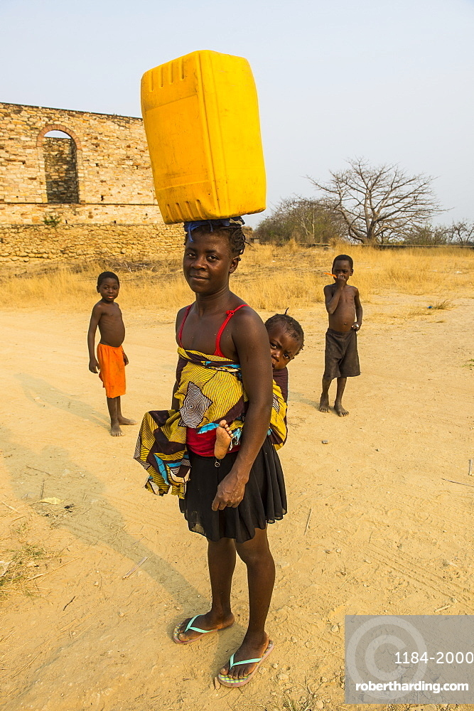 Woman with her baby on her back carrying a water canister on her head, Massangano, Cuanza Norte, Angola, Africa