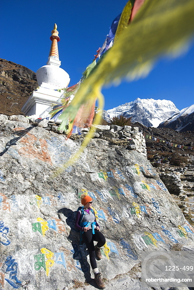 A woman trekking in the Langtang valley stops near a colorful Mani Stone wall below a Stupa decorated with Buddhist prayer flags, Langtang Region, Himalayas, Nepal, Asia