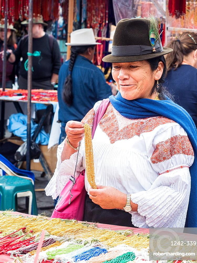 Indigenous woman buying gold necklace, market, Plaza de los Ponchos, Otavalo, Ecuador, South America