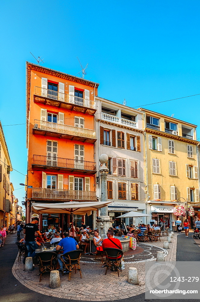 Tourists at a cafe on a street corner and traditional Provencal architecture in Antibes, Cote d'Azur, Provence, French Riviera, France, Europe