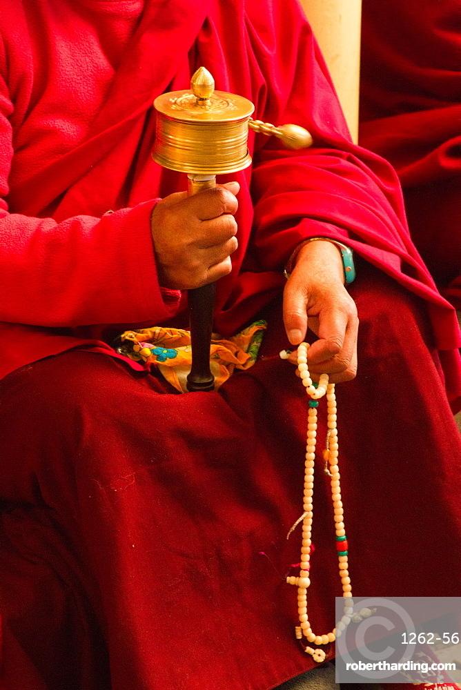 Tibetan Buddhist monk with prayer wheel and beads at Losar (Tibetan New Year) in the Dalai Lama Temple, McLeod Ganj, Dharamsala, Himachal Pradesh, India, Asia