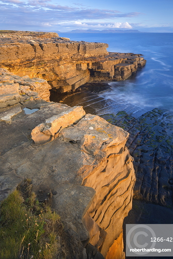 Limestone cliffs lit by low angled evening light on the Wild Atlantic Way at Muckross Head, Co Donegal, Republic of Ireland