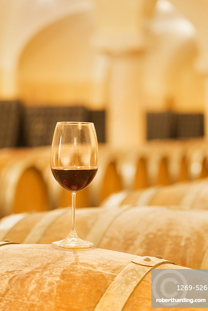Wine glass exposed on a wood barrel. Buglio in Monte, Valtellina, Lombardy, Italy, Europe.