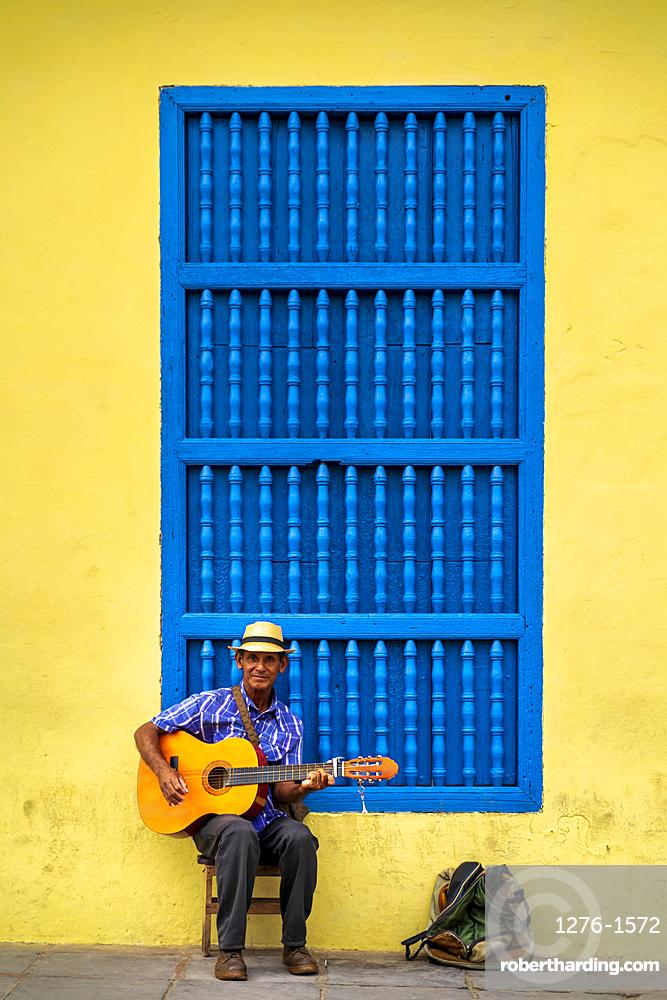 An elderly Cuban sitting on a chair. playing a guitar, Trinidad, Sancti Spiritus Province, Cuba, Central America