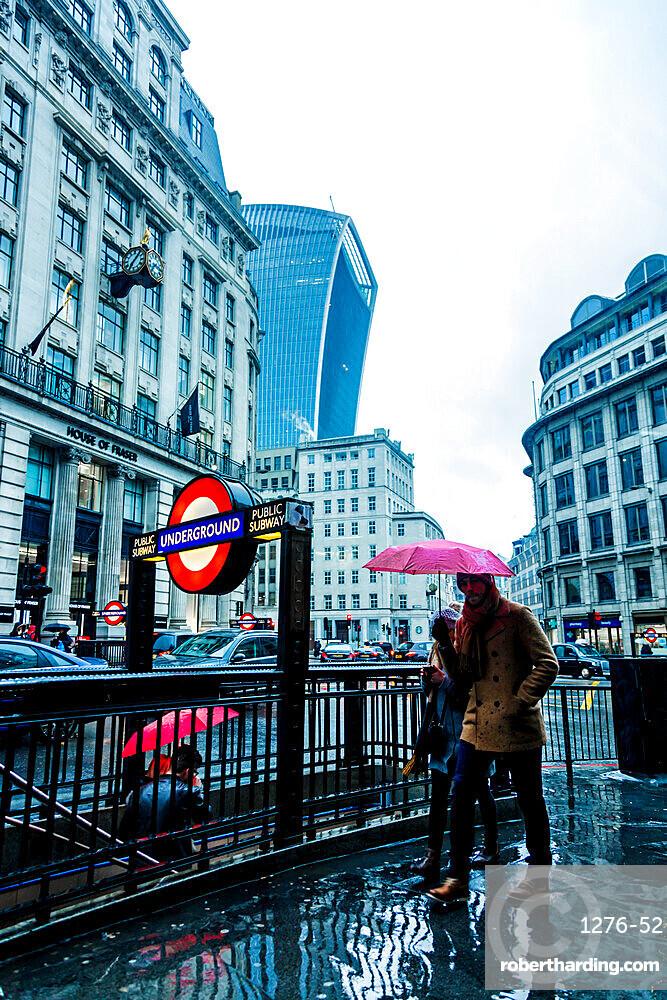 Underground sign and people entering entering tube station on a rainy day, London, England, United Kingdom, Europe