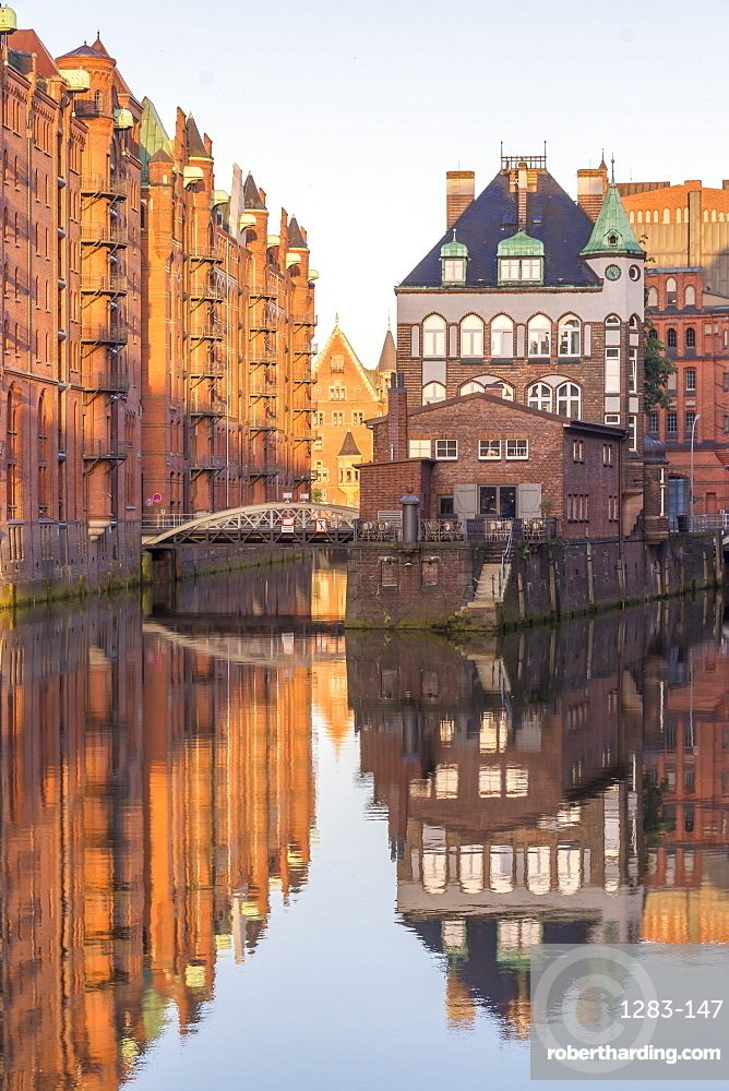 Wasserschloss building at the historical warehouse complex (Speicherstadt) seen from Poggenmuehlenbruecke at sunrise, Hamburg, Germany, Europe