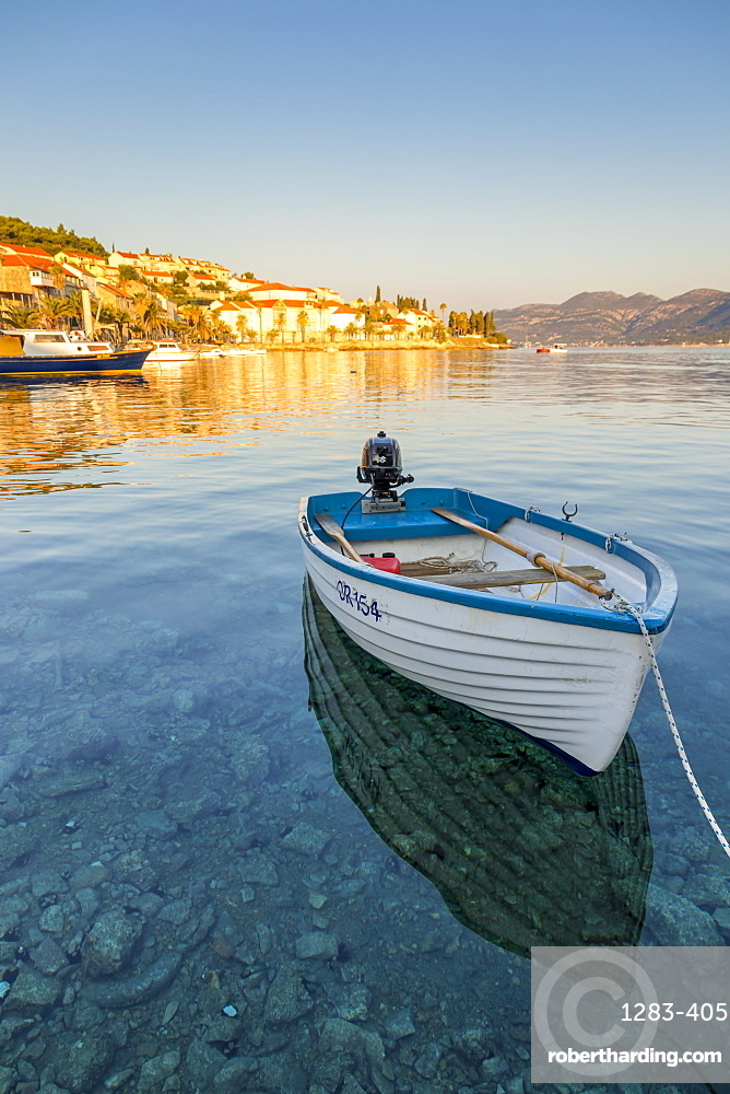 Small boat anchoring outside the old town at first sunlight, Korcula Town, Croatia, Europe