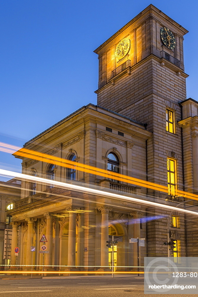 The clock tower of the Hamburg Chamber of Commerce building with traffic light trails during dusk