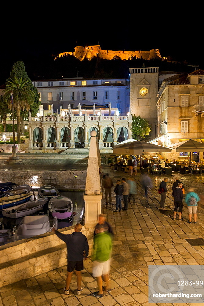 Night shot of the main square (Trg Svetog Stjepana) of Hvar Town with view to the Spanish Fortress in the background