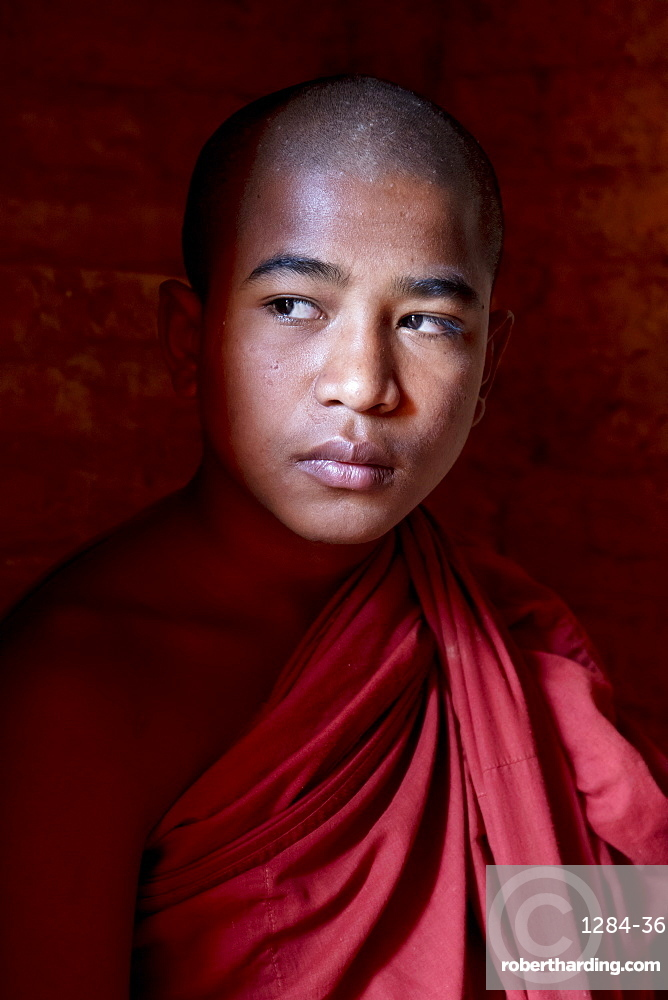 Young monk in the shadows at a temple in Bagan, Myanmar (Burma), Asia