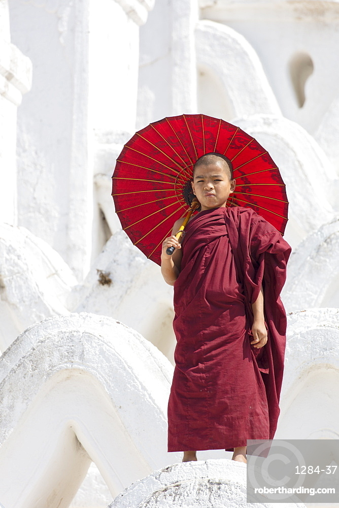 Young monk dressed in red, with red parasol at the Myatheindan Pagoda (White Temple) in Mingun, Myanmar (Burma)