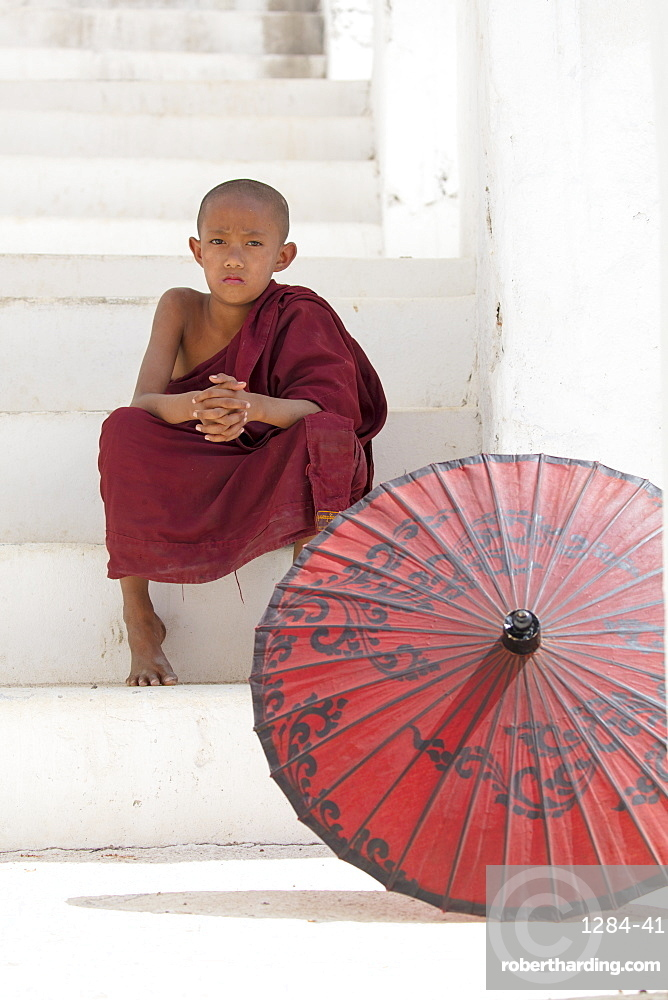 Young monk dressed in red, sits on steps with red parasol at the Myatheindan Pagoda (White Temple) in Mingun, Myanmar (Burma)