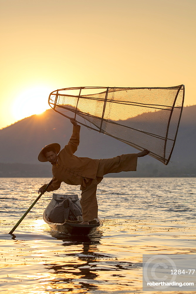 A fisherman standing on one leg and holding his fishing net at sunset on Inle Lake, Shan State, Myanmar (Burma), Asia