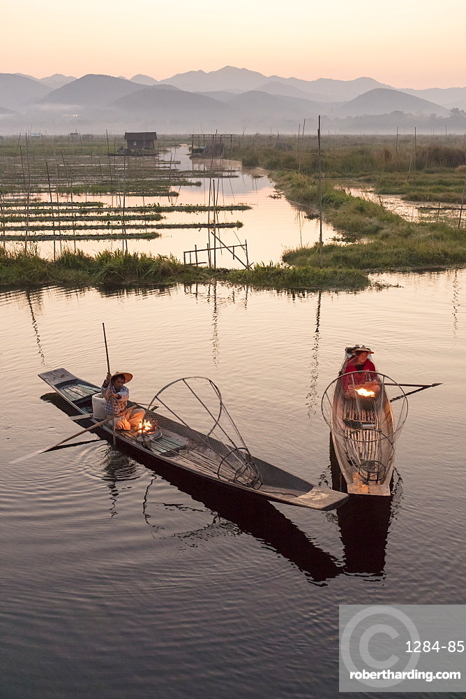 Two fishermen keep warm in their long tail fishing boats at dawn near the floating gardens on Inle Lake, Shan State. Myanmar (Burma), Asia