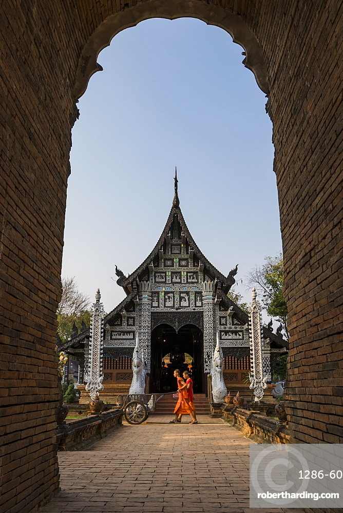 Temple Wat Lok Moli seen through an arch with two monks walking by, Chiang Mai, Thailand, Southeast Asia, Asia