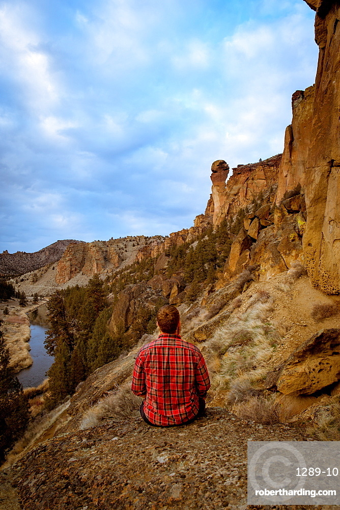 Man wearing a flannel shirt looking at a large rock formation, Oregon, United States of America, North America