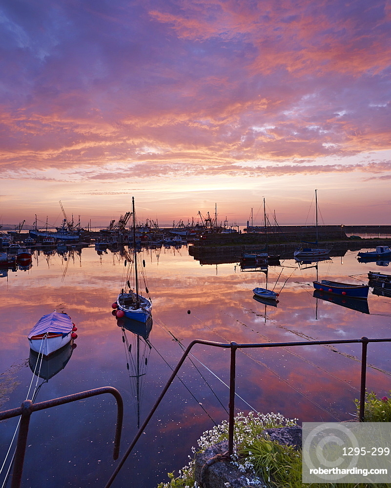 Dawn twilight with underlit clouds, reflections and moored boats in the harbour of the fishing port of Newlyn in Cornwall, England, United Kingdom, Europe