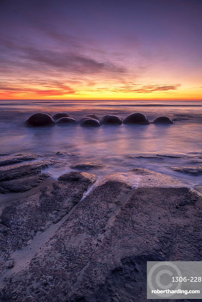Epic sunrise at Moeraki Beach with the Moeraki Boulders, Moeraki Beach, Otago, New Zealand.