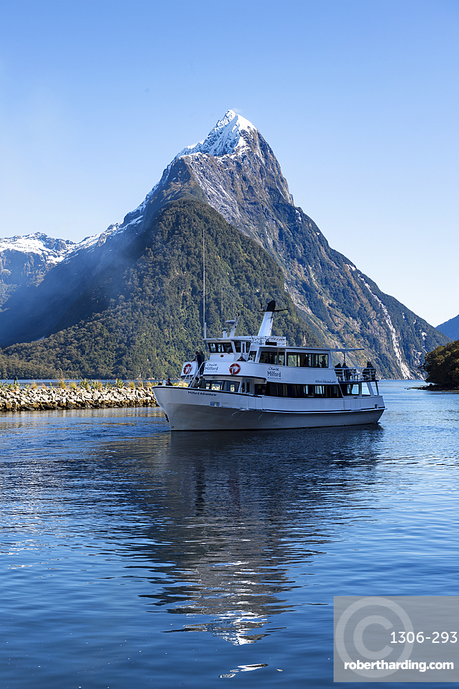 Milford Adventurer Cruise ship at Milford Sound with snow capped Mitre Peak, Fiordland National Park, New Zealand
