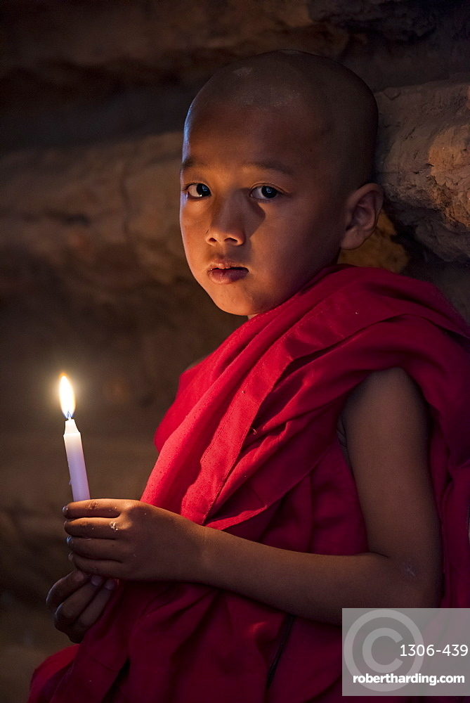 A young Buddhist monk holding candle at temple, Bagan (Pagan), Myanmar (Burma), Asia