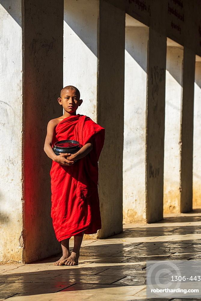 Novice Buddhist monk holding a bowl in Shwezigon Pagoda in Nyaung U., Bagan (Pagan), Myanmar (Burma), Asia