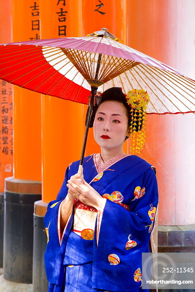 Portrait of a geisha holding an ornate red umbrella in front of a line of red torii gates, Fushimi-Inari Taisha, Kyoto, Kansai Region, Honshu, Japan, Asia