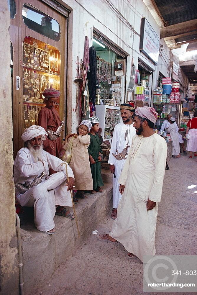 People gathered outside souk, Nizwa, Oman, Middle East