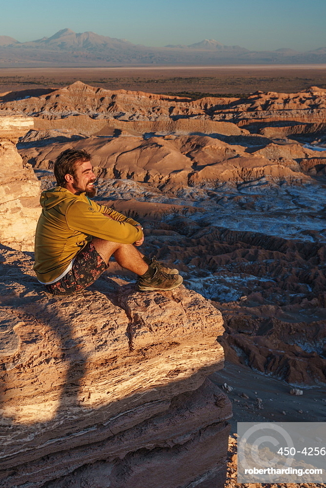 Happy hiker enjoying the view at sunset across Death Valley, near San Pedro de Atacama, Chile, South America