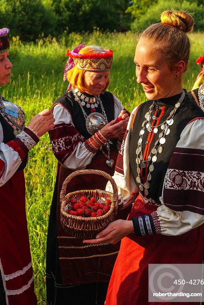 Seto girl offers wild strawberries to friends, Feast Day, Uusvada, Setomaa, SE Estonia, Europe
