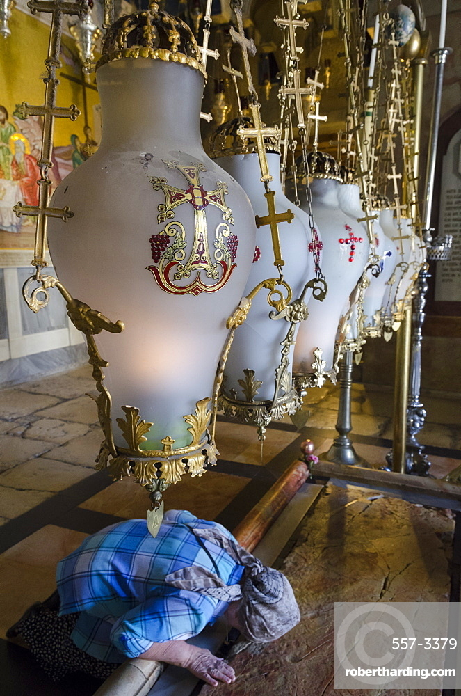 Close up of traditional lamps hanging above the Stone of Anointing with woman prostrating, Church of the Holy Sepulchre, Old City, Jerusalem, Israel, Middle East