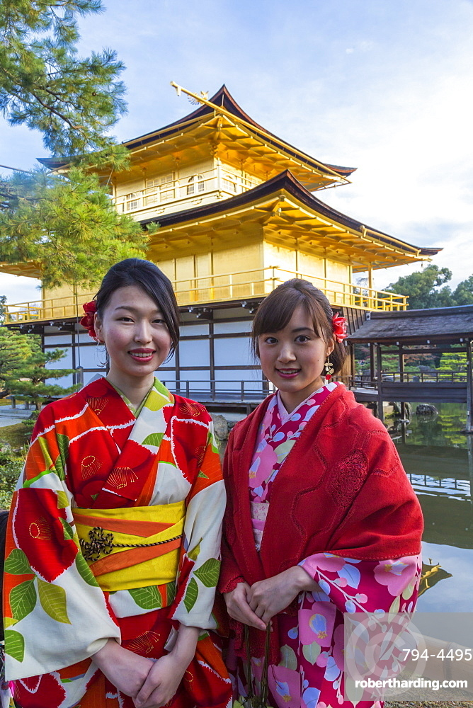 Women in traditional Japanese kimonos in front of the Golden Pavilion temple (Kinkaku-ji) in Kyoto, Japan, Asia
