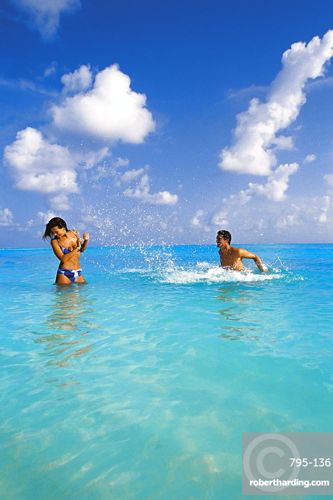 Couple splashing in the sea, Maldives, Indian Ocean, Asia
