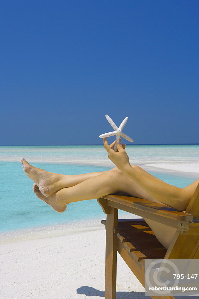 Woman holding seastar on the beach, Maldives, Indian Ocean, Asia