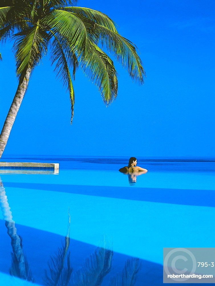 Woman in swimming pool under palm tree looking at sea, Maldives, Indian Ocean, Asia