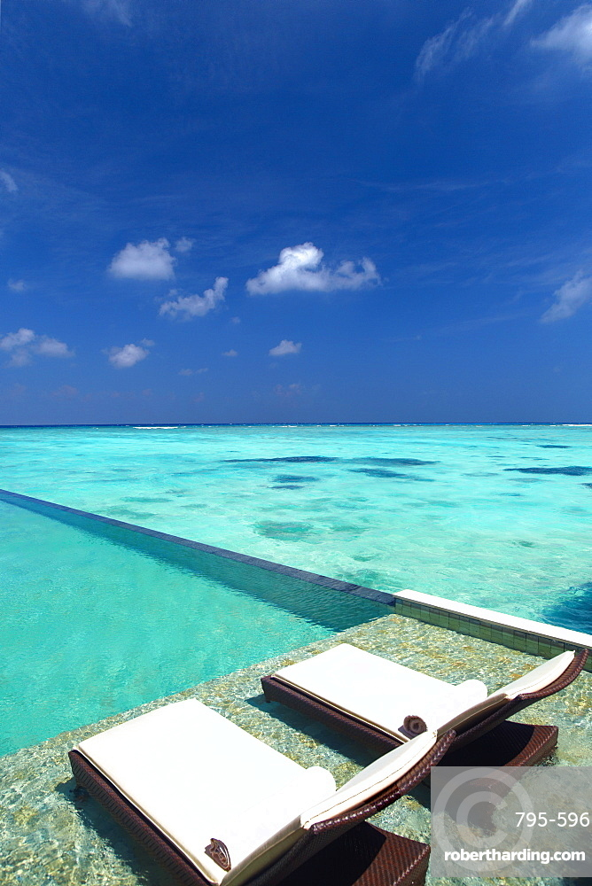 Lounge chairs on infinity pool and tropical beach, The Maldives, Indian Ocean, Asia