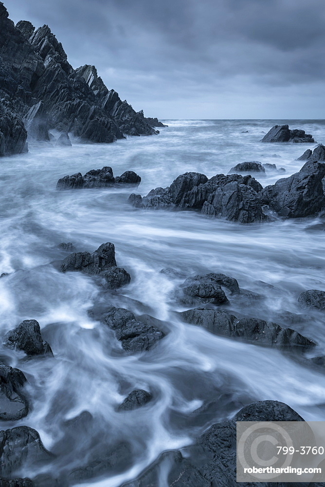 Swirling waves over dark rocks in a rugged North Devon cove, England. Winter (January) 2019.