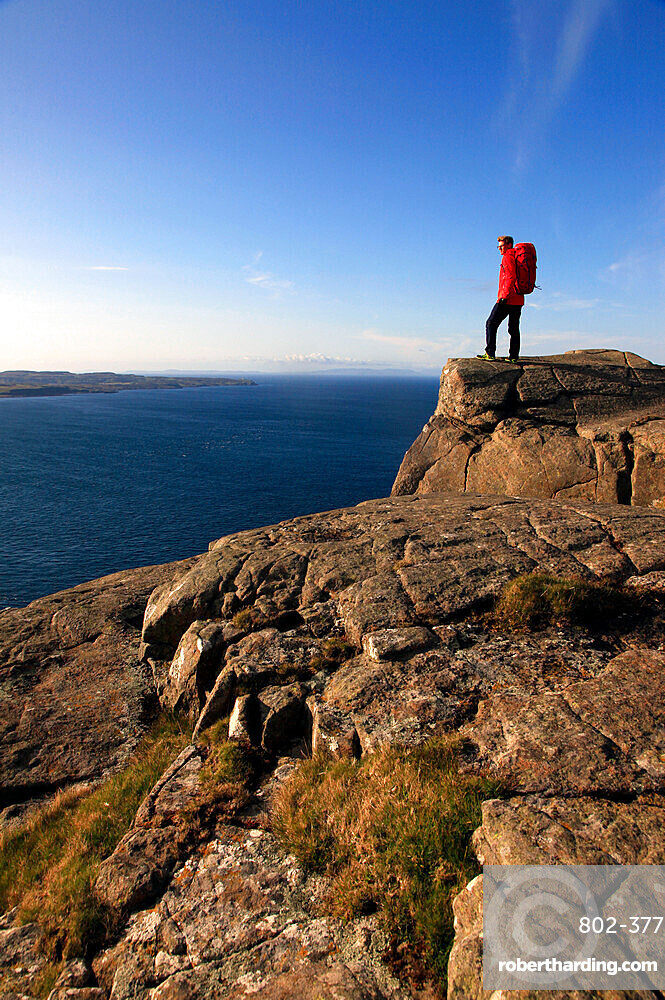 A hiker looks out to sea from cliffs at Fair Head, Northern Ireland