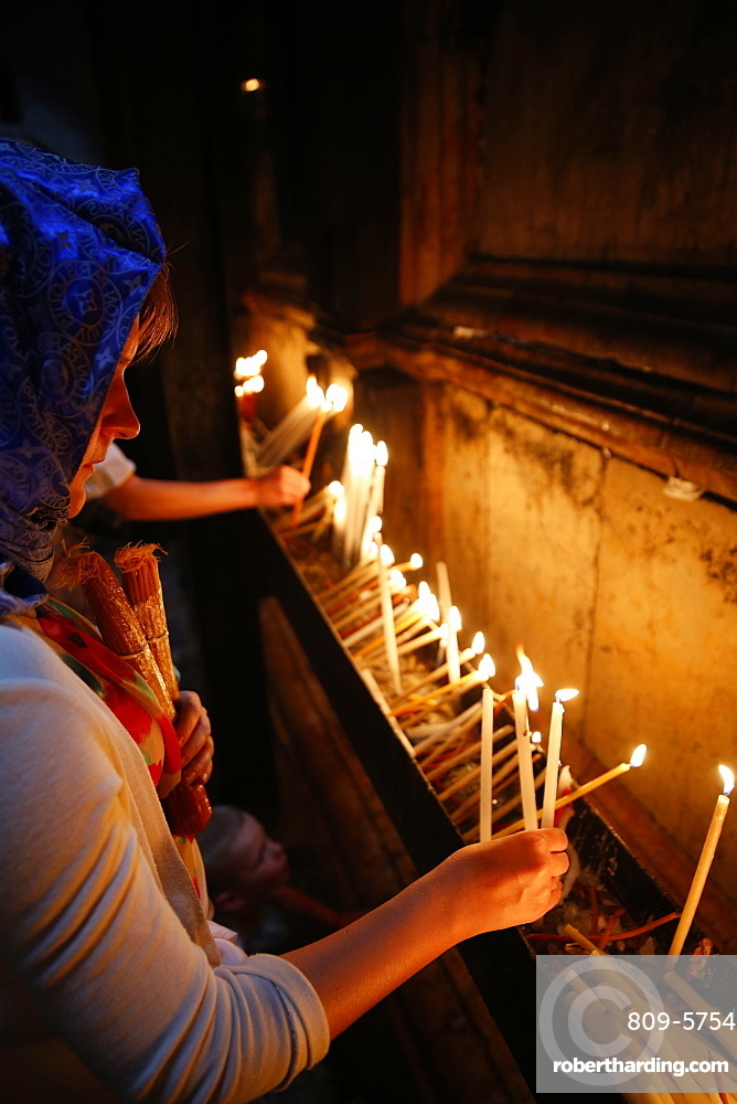 Pilgrims lighting candles in the Holy Sepulchre Church, Jerusalem, Israel, Middle East