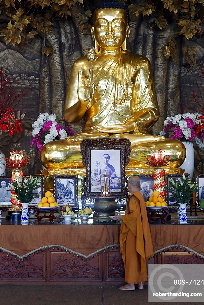 Golden Buddha with lotus flower and Buddhist monk, Minh Dang Quang Buddhist Temple, Ho Chi Minh City, Vietnam, Indochina, Southeast Asia, Asia