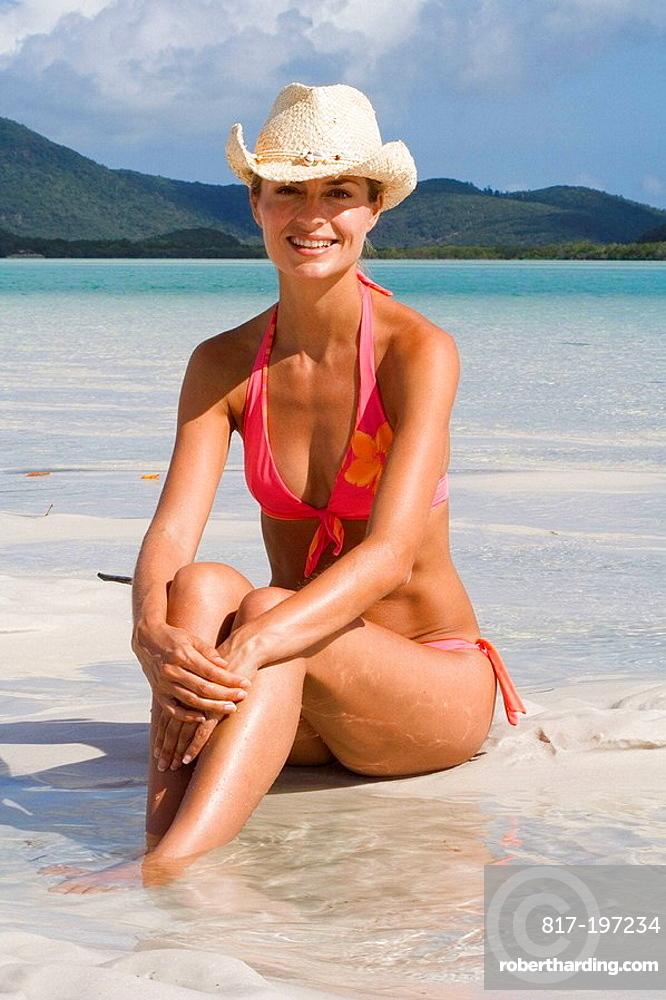 Portrait of woman in bikini and cowboy hat, Whitehaven Beach, Australia