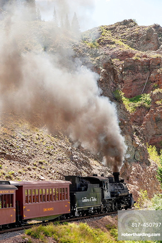 USA, New Mexico, Chama. The Cumbres and Toltec Scenic Railroad. Steam train climbs through rock canyon.