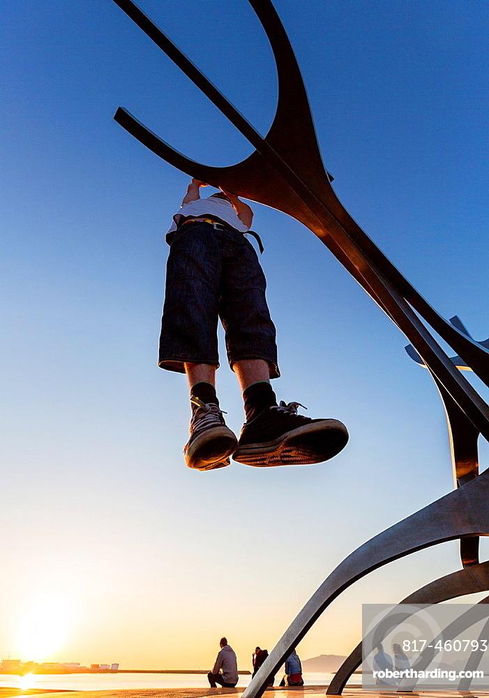 Teenager hanging on metal sculpture known as The Solfar, Reykjavik, Iceland.