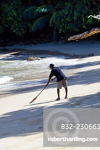 Creole cleaning the beach, Mahe Island, Seychelles, Indian Ocean, Africa
