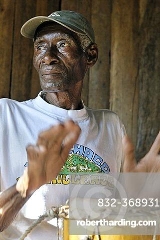 Old man, Afro-Colombians, playing a barrel drum, Bajamar slum, Buenaventura, Valle del Cauca, Colombia, South America