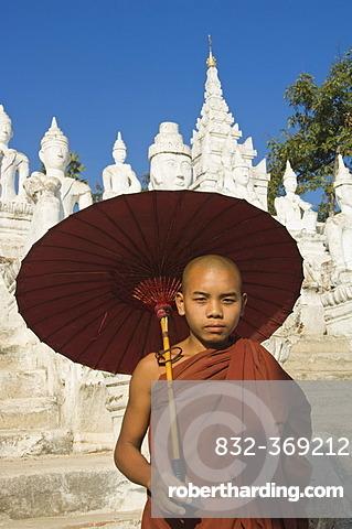 Young Buddhist monk with a red umbrella, Settawya Pagoda, Mingun, Burma, Myanmar, South East Asia