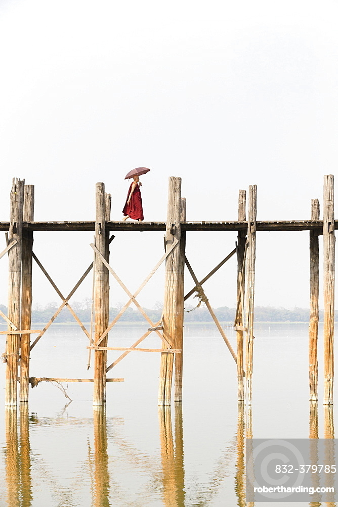Monk crossing U Bein bridge, Taungthaman Lake, Mandalay region, Myanmar, Asia